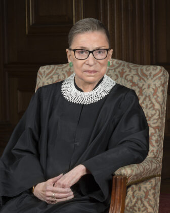 RBG in black robe and lace collar looking serious and dignified